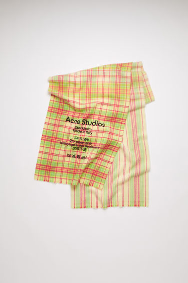 Acne Studios fuchsia/yellow scarf is crafted to a slim dimension from soft wool that's woven with tartan checks and features a large-scale logo and care instruction print on front.