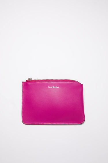 Acne Studios fuchsia pink zip wallet is made of soft leather and accented with a silver-tone zipper closure and silver logo stamp on the front.