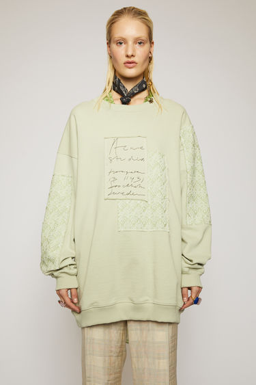 Acne Studios pastel green sweatshirt is cut to an oversized fit and patched with jacquard denim to enhance a well-worn look. It shaped with a ribbed crew neck and features a handwritten logo embroidered across the chest.