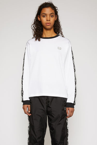Acne Studios optic white long-sleeved t-shirt is crafted from midweight cotton jersey with contrasting ribbed collar and cuffs and features face-jacquard stripe panels along the sleeves.