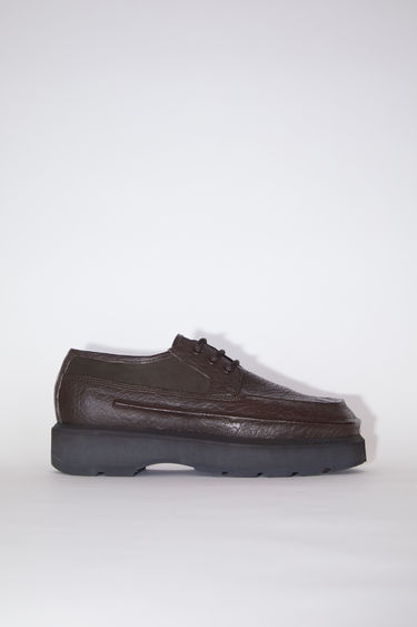 Acne Studios coffee brown lace-up derby shoes are made of leather, inspired by boat shoes.