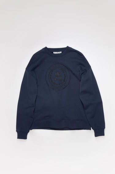 Acne Studios navy crew neck sweatshirt is made of cotton with an embroidered design on the front.