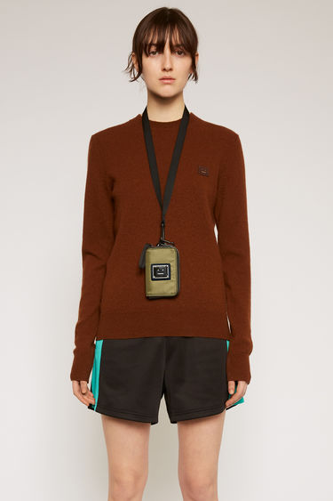 Acne Studios dark brown sweater is knitted in a fine gauge from soft wool yarns and accented with a tonal face-embroidered patch on the chest.