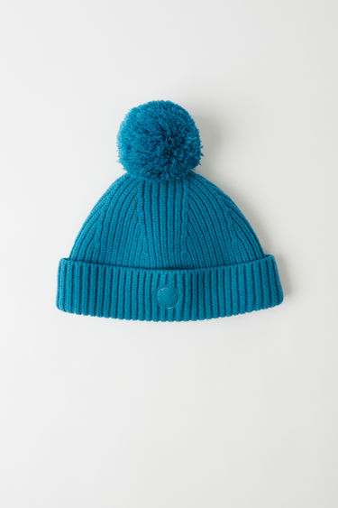Acne Studios ocean blue beanie is crafted from ribbed wool-blend with a rounded crown that's topped with a detachable bobble and is finished with a logo patch on the cuff.