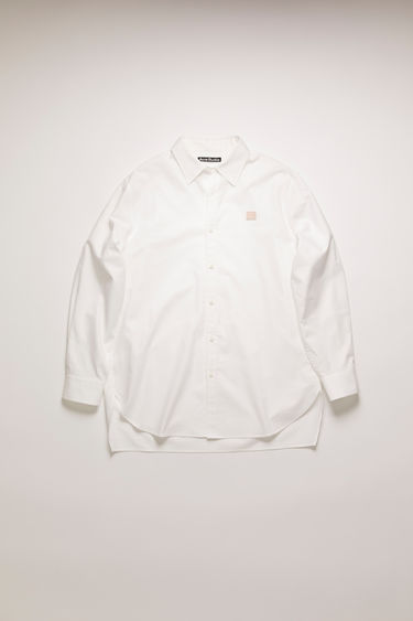 Acne Studios white oxford shirt is crafted from organic cotton to a boxy shape with an oversized fit and finished with a button-down front closure and a contrasting face-embroidered patch on the chest.