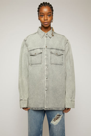 Acne Studios stone grey overshirt is crafted from rigid denim that's stonewashed for a worn-in look. It's cut to a relaxed fit with dropped shoulders and accented with antiqued metal snap buttons.