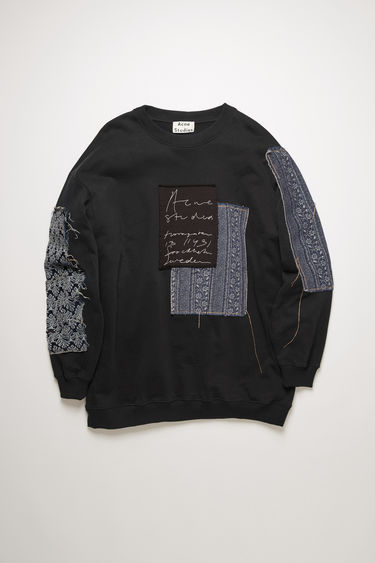 Acne Studios black sweatshirt is cut to an oversized fit and patched with jacquard denim to enhance a well-worn look. It shaped with a ribbed crew neck and features a handwritten logo embroidered across the chest.