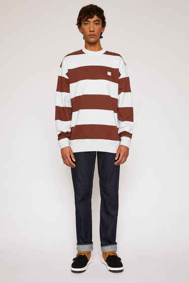 Acne Studios cognac brown fleece sweatshirt is patterned with block stripes and finished with a face-embroidered patch on the chest.