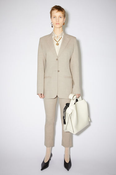 Acne Studios beige constructed suit jacket is made of wool with a slight stretch, featuring a fitted waist and elongated silhouette.