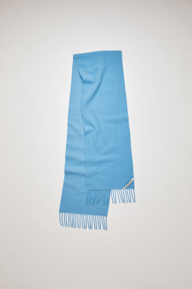 Acne Studios aqua blue scarf is crafted from soft wool that's pilled on one side and finished with fringed ends and a logo label across one corner.