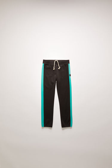 Acne Studios black track pants are crafted from lustrous technical jersey with contrasting stripes down the sides and shaped with an elasticated waistband.