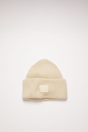 Acne Studios cream beige beanie is knitted in a thick rib-stitch from soft wool and features a tonal face-embroidered patch on the turn-up.