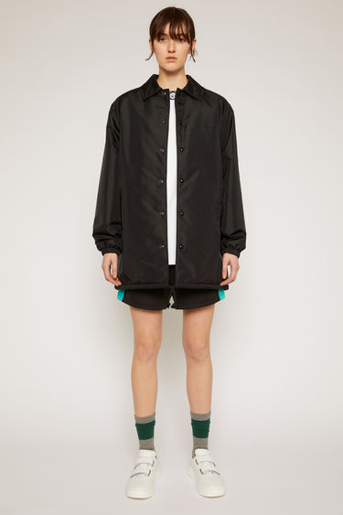 Acne Studios black coach jacket is crafted from technical shell filled with insulating padding and features a face motif across the back and front.
