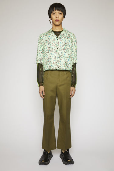 Acne Studios olive green trousers are cut from technical cotton twill with bootcut legs and finished with pressed creases and raw edges on the waistband.