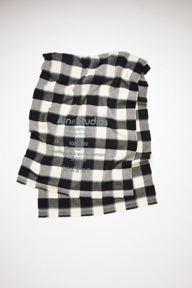 Acne Studios grey/black/white oversized, checked scarf is made of wool with a large, printed care label.