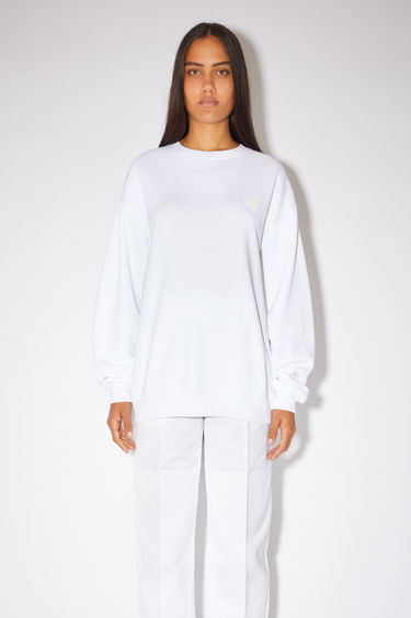 Acne Studios optic white sweatshirt is crafted from midweight loopback fleece to a loose silhouette and finished with a face-embroidered patch on the chest.