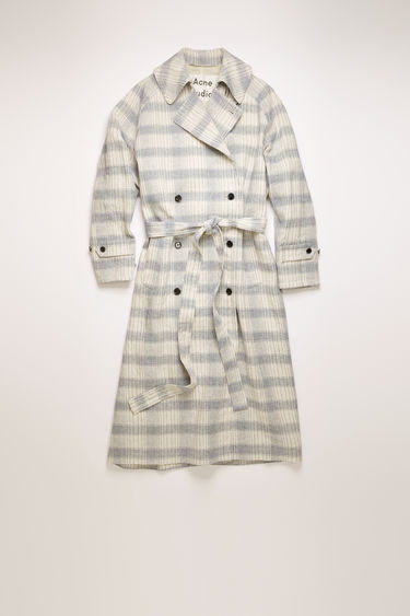 Acne Studios beige/blue double-breasted trench coat is crafted from a cotton and linen blend and woven with a checked pattern. It's cut to a raglan-sleeved silhouette and features a matching belt and an oversized back storm flap.