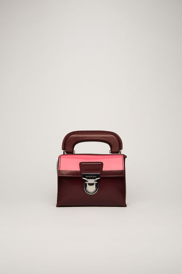 Acne Studios burgundy mini satchel bag is crafted from smooth calf leather with a subtle debossed logo on the front and a neat flap and accented with silver-tone metal hardware.