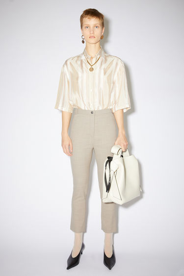 Acne Studios beige suit trousers are made of wool with a slight stretch and have a high waist and skinny fit with cropped leg length