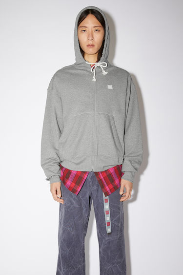 Acne Studios light grey melange relaxed hooded sweatshirt is made of organic cotton with a face patch and ribbed details.