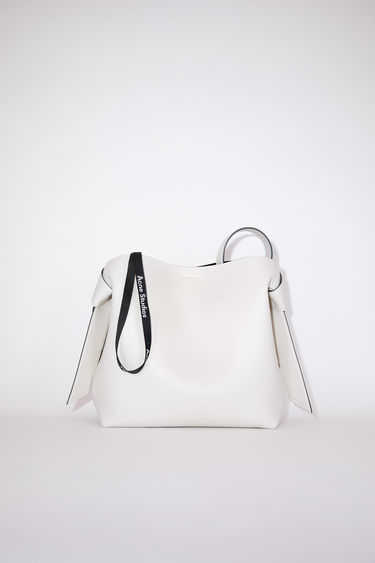 Acne Studios white/black medium bag features twisted knots inspired by traditional Japanese obi sashes. It has a debossed logo and snap button closure, which opens to reveal a zipper compartment for storing small essentials.