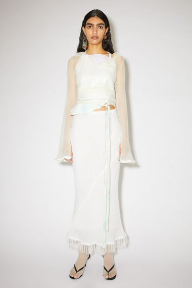 Acne Studios white linen skirt is cut on the bias with fringed accents.