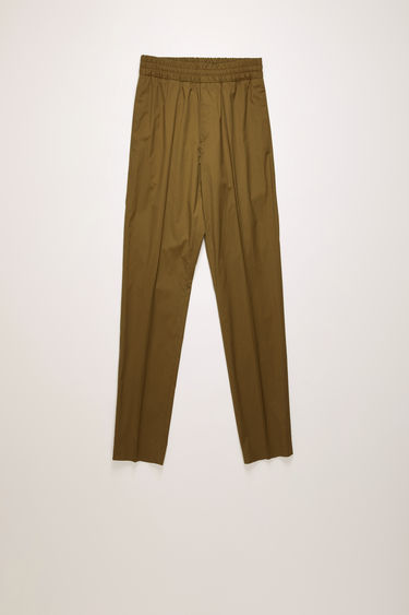 Acne Studios hunter green trousers are made from cotton with a sheen finish and shaped with slim legs with a mid-rise elasticated waistband.