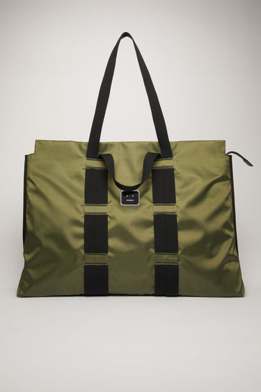 Acne Studios khaki green tote bag is crafted from technical ripstop and features two different cotton-canvas handles that's woven on the body of the bag. It's finished with a zip-top fastening that opens to reveal a spacious interior with a mesh pocket and key ring.