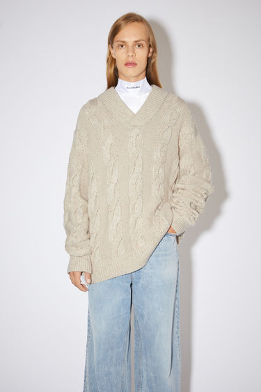 Acne Studios beige melange chunky kabel knit sweater is made of a cotton blend and features a shawl collar.