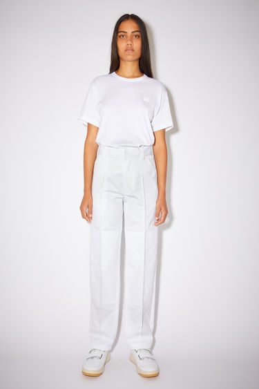 Acne Studios white classic workwear trousers are made of a cotton twill blend with creased legs and a leather face patch.