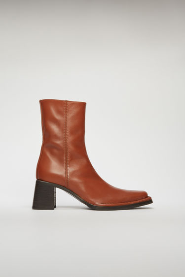 Acne Studios brown/brown mid-calf boots are crafted to a pointed toe from supple leather and set on a stacked block heel. They are finished with thick topstitching and a zip closure on the side.