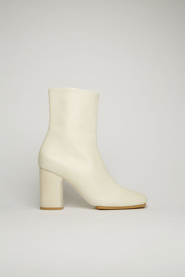 Acne Studios off white ankle boots are crafted from soft lamb leather to a square-toe shape and set on a high block heel and durable rubber sole.