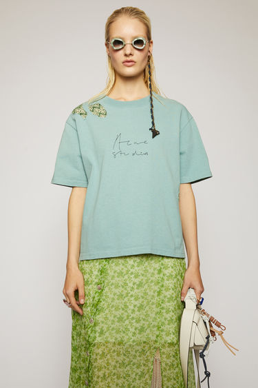 Acne Studios turquoise blue t-shirt is cut to an oversized fit and patched with jacquard denim to enhance a well-worn look. It shaped with a ribbed crew neck and features a handwritten logo embroidered across the chest.