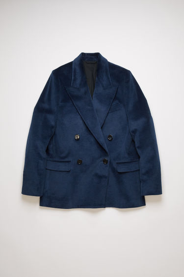 Acne Studios ink blue corduroy suit jacket is crafted to a double-breasted silhouette and finished with wide notch lapels and two front flap pockets.