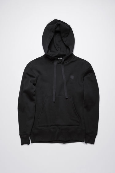 Acne Studios black hooded sweatshirt is made of organic cotton with a face logo patch and ribbed details.