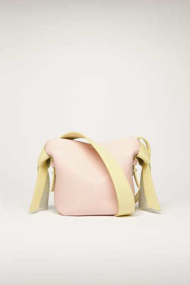 Acne Studios Musubi Mini pale pink/ pale yellow bag features twisted knots inspired by the formation of traditional Japanese obi sash. It's crafted from soft grain leather and has a central zipped divider to store small essentials.