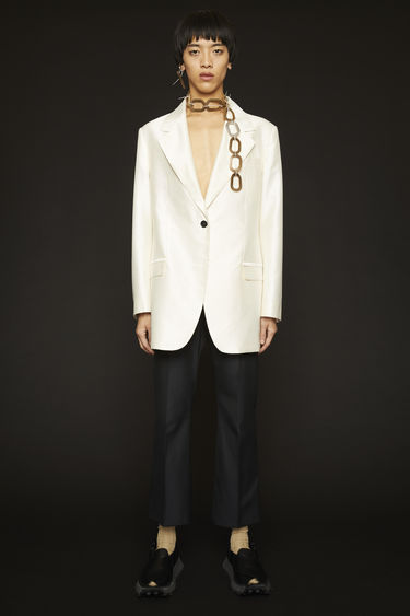 Acne Studios white suit jacket is crafted from a high-shine cotton blend suiting and features padded shoulders and mismatched buttons.