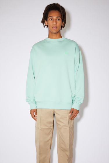Acne Studios spearmint green sweatshirt is made of organic cotton with a face logo patch and ribbed details.