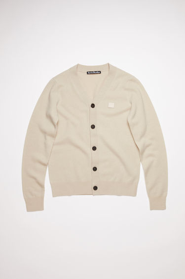 Acne Studios cream beige v-neck cardigan sweater is made from wool with a face logo patch and ribbed details.