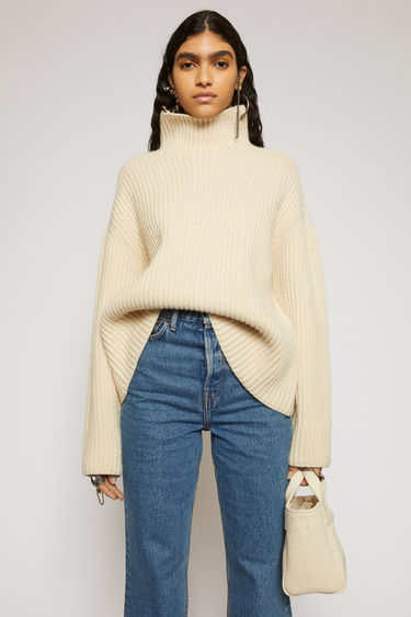 Acne Studios oat beige sweater is knitted from wool in a chunky ribbed pattern. It's accented with a fully fashioned high neck, shoulders and slightly rounded sleeves to define the boxy silhouette.