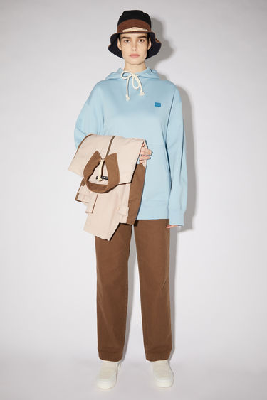 Acne Studios powder blue oversized hooded sweatshirt is made of organic cotton with a face patch and ribbed details.