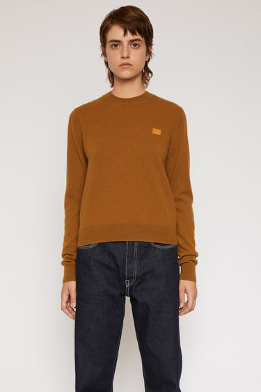 Acne Studios caramel brown sweater is finely knitted from pure wool and finished with a tonal face-embroidered patch and ribbed trims.