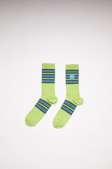 Acne Studios green/blue striped socks are made of a cotton blend knit with ribbed and face patch details.