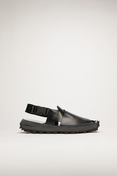 Acne Studios black/black/black sandals are inspired by traditional Peshawari Chappal. They're crafted from high-shine leather with wide cross-over straps and set on a stacked tread sole.