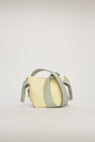 Acne Studios Musubi Micro pale yellow/pale blue bag features knotted details inspired by the traditional Japanese obi sash. It's crafted from soft grain leather and comes equipped with a detachable shoulder strap and a top handle.