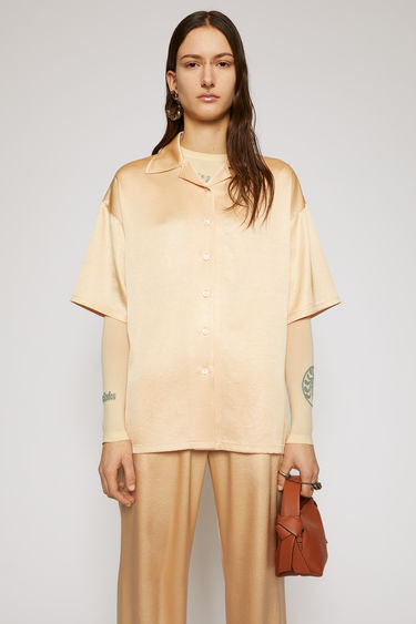 Acne Studios pale orange satin shirt is cut to a boxy silhouette with an open collar and short sleeves and finished with tonal buttons through the front.