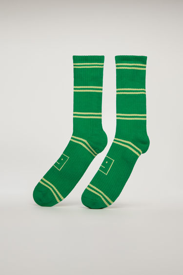 Acne Studios green multi striped socks are knitted from cotton-blend and features a face motif jacquard and soft towelling interior.