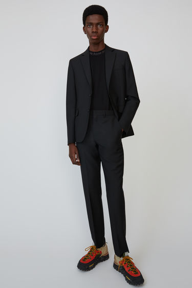 Acne Studios black fitted, tapered leg trousers.