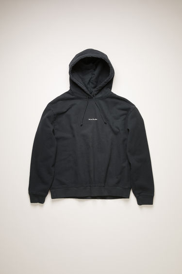 Acne Studios black hooded sweatshirt is made from organic cotton that's lightly faded along the seams. It's cut to a relaxed silhouette with dropped shoulders and ribbed edges and features a raised logo print on front.