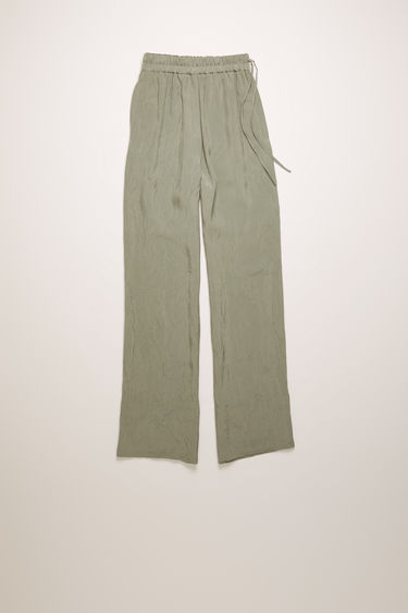 Acne Studios silver grey trousers are crafted from a lightweight crinkled viscose and shaped with loose, straight legs with an elasticated waistband.